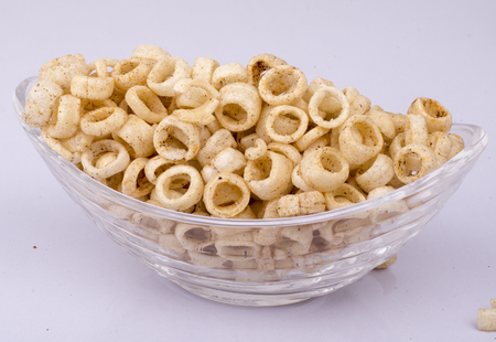 Spicy fryums or snacks, or corn rings in glass bowl