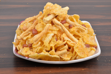 traditional indian corn flakes namkeen with peanuts in white plate