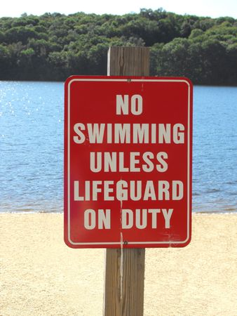 no swimming: no swimming unless lifeguard on duty sign on beach
