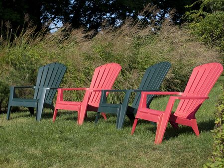 green and red adirondack chairs in a row facing the horizon photo