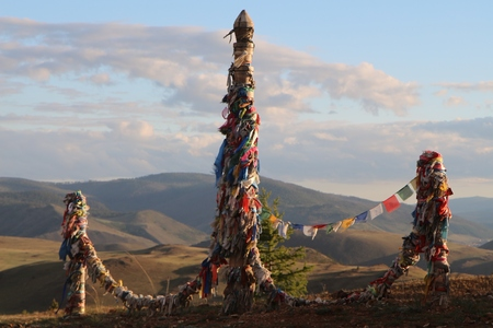 Ritual poles erected by shamans in steppe near lake Baikal, Russia; colored ribbons represent offerings by believers to holy spirits Stock Photo