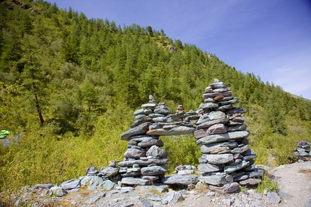 Stones stacked in a high pyramid in the mountain forest Stock Photo