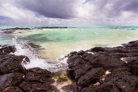 waves crushing at Lava rocks on beach of the tropical volcaninc island of Mauritius Reklamní fotografie
