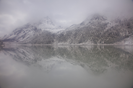 snow-covered Altai mountains reflect in Akkem lake on a cloudy day; Russia Reklamní fotografie