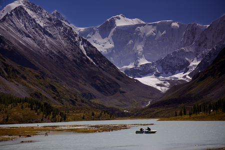 a boat with tourists crosses a lake surrounded by snow topped mountains of Altay, Russia, near border with Kazakhstan
