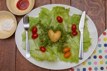 Heart shaped potato on dark wooden table.