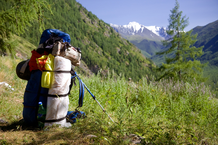 A rucksack in the grass with mountains in the background Reklamní fotografie