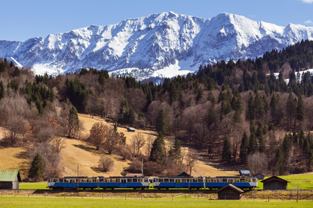 A train passes farm fields and barns near town of Garmisch Partenkirchen in Bavaria, Germany; forest and snow covered Alpes in background