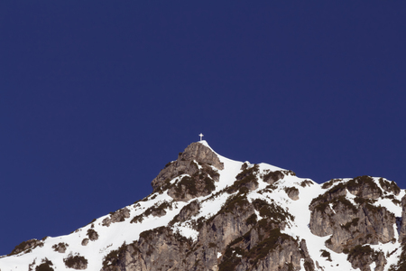 Garmisch-Partenkirchen, Germany - April 7, 2018 - white cross on the top of one of the mountains surrounding the popular skiing resort Garmisch-Partenkirchen