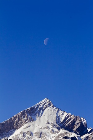 moon on the blue sky over snow covered mountain peaks