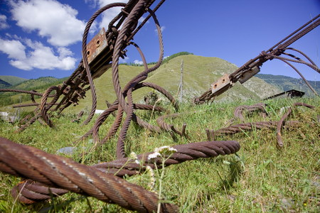 old rusty steel wires lay tangled twisted in the grass under blue
