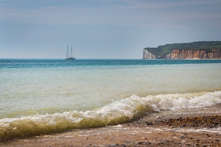 waves on a sandy beach, boat in the sea and britich coast cliffs in the background