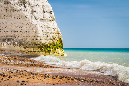 waves crushing on a beach with white chalk cliffs in the background, south coast of the UK