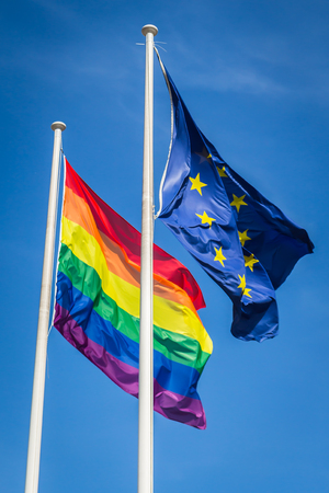 Rainbow flag and EU flag waving in the wind, sunny day, blue sky Reklamní fotografie