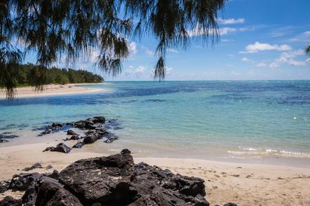 blue ocean and black lava stones on a sandy beach of volcanic island Mauritius Reklamní fotografie