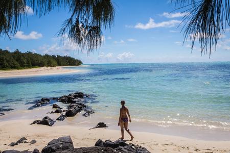 A woman walks on a beach Reklamní fotografie
