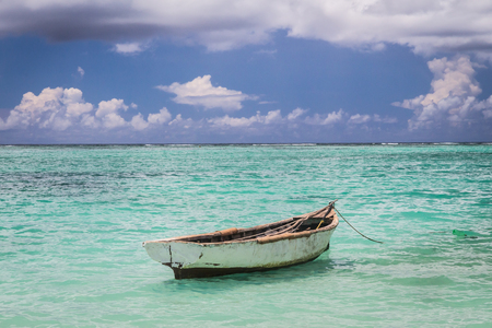 old fisherman boat moored in the blue ocean under cloudy sky, Mauritius island Reklamní fotografie