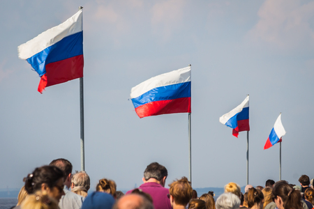 Saint Petersburg, RUSSIA - July 22, 2018: Russian flags flying over the heads of people in the crowd on a street Redakční