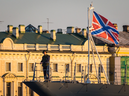 SAINT-PETERSBURG, RUSSIA, July 24, 2018: navy sailor on the bow of a ship moored on Neva river in front of Senate and Synode historical building