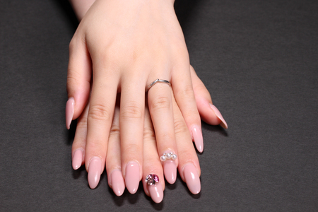Stylish trend female manicure. Beautiful young womans hands on black background.