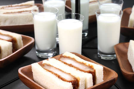 pork cutlet sandwich and glass of milk reflecting in the mirror Imagens