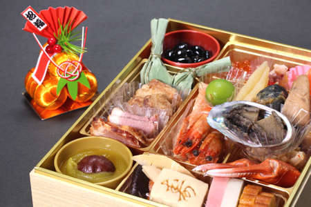 Japanese New Year dishes Osechi. letters meaning congratulations and Blessing Imagens