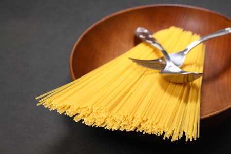 Raw dry spaghetti on a plate on black background Imagens