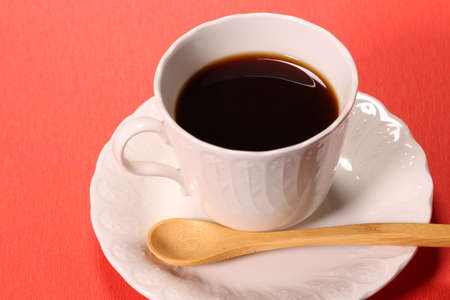 Coffee in a cup on red background