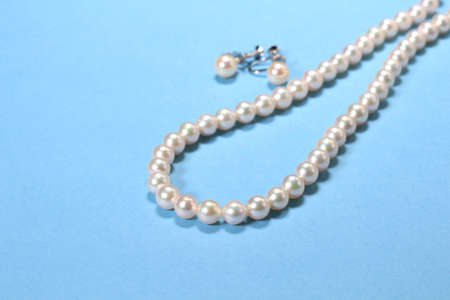 Pearl Necklace and earrings on blue background