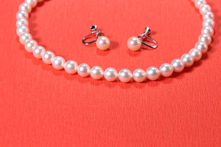 Pearl Necklace and earrings on  red background