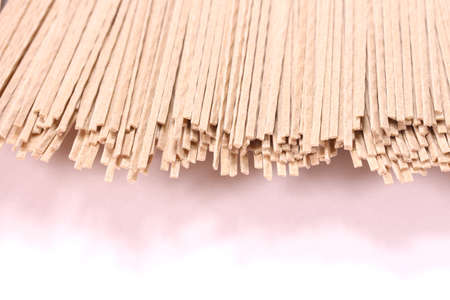 Uncooked soba noodles on white background