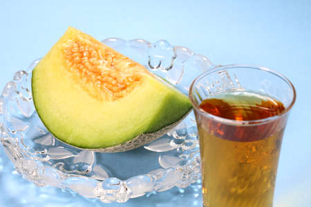 Cut melon and glass of barley tea on blue background