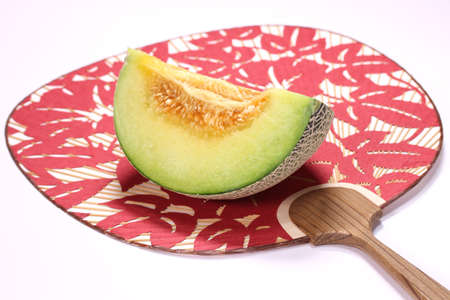 Cut melon and japanese fan on white background