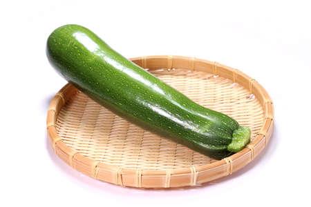 fresh green zucchini on a colander on white background Banco de Imagens