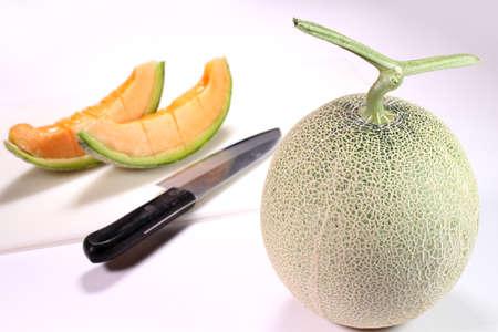 Fresh ripe melon and cutting board, kitchen knife Banco de Imagens
