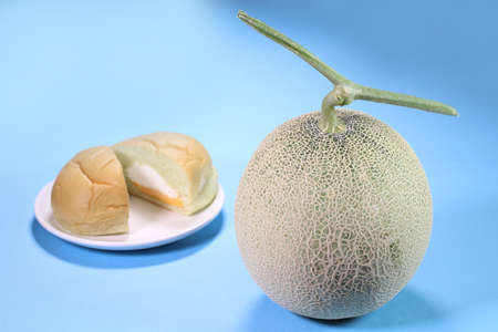 Muskmelon and melon bread on blue background