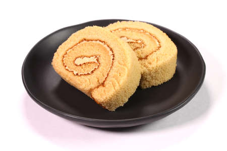 Roll cake with coffee cream on a plate on white background