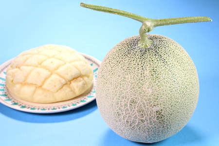 Cantaloupe melon and melon bread on blue background