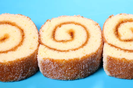 Roll cake with apricot jam on blue background