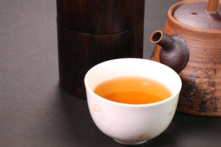 Hojicha, roasted green tea, a  cup of tea, tea pot and tea canister
