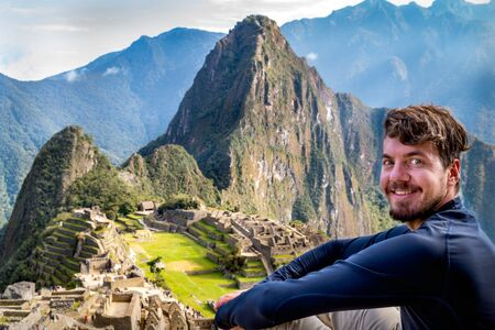 A man posing in Machu Picchu. You can see the ruins of the citadel of Machu Picchu, the Huayna Picchu mountain and the great Andes mountains behind. 写真素材