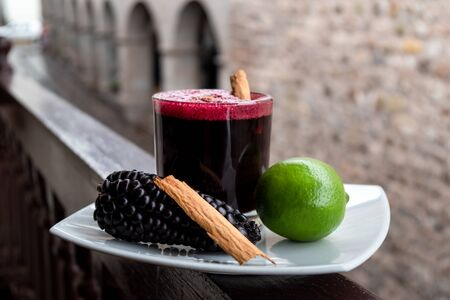 Chicha morada. Peruvian drink, decorated with lime, a piece of cinnamon and chicha fruit 免版税图像