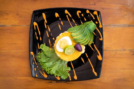 Traditional Peruvian dish called Causa Limeña made with mashed potatoes, vegetables, avocado and eggs