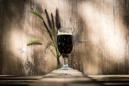 Glass of black beer with foam. Wooden background with streaks and spikes behind.