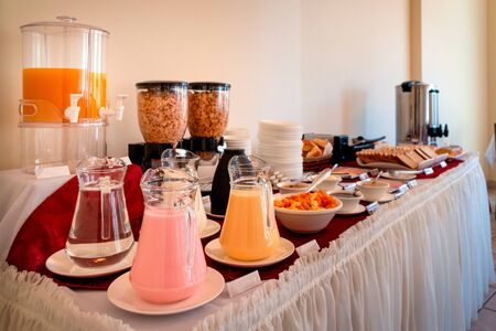 Table full of food for a buffet breakfast. Among those that can be seen: orange juice, cereals, yogurt jars, jams, fruits, coffee dispenser and toast