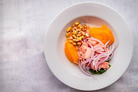 Pyszne i świeże ceviche podawane z cebulą, batatami, prażoną kukurydzą i sałatą. Kuchnia latynoska. Białe tło. Widok z góry