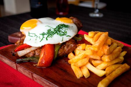 Juicy meat accompanied with sauteed vegetables fried egg and french fries, all served on a wooden board