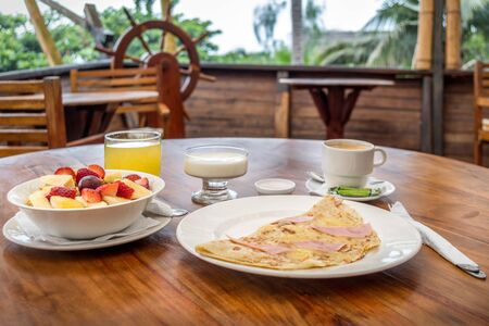 breakfast served on a wooden table. You can see a cup of coffee, a glass of yogurt, orange juice, a plate with several fruits and a plate with an omelet Reklamní fotografie