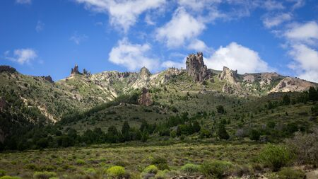 Mountain of rocky peaks, background of blue sky and white clouds. You can see a valley full of vegetation and very colorful. Villa Traful, Patagonia Argentina Standard-Bild