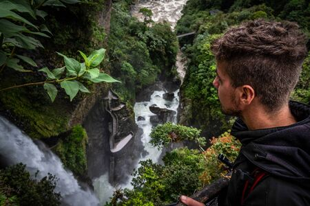 R?o Verde waterfall or also called Pail?n del Diablo waterfall. A tourist who contemplates the incredible and powerful waterfall surrounded by a tropical forest. You can see its emblematic staircase. Ecuador